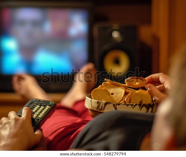 Woman eating unhealthy snacks in front of a television
