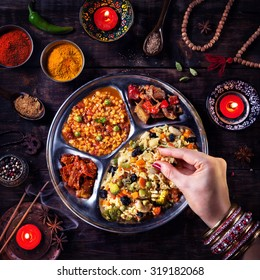Woman eating vegetarian biryani by her hand with bangles near candles, incense and religious symbols at Diwali celebration