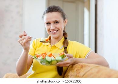 woman eating veggie salad with spoon on sofa