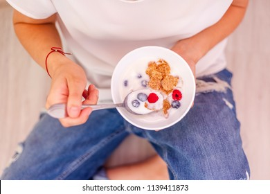A woman is eating yogurt with cereal and berries for breakfast, holding a spoon, close-up hands, a healthy diet and a diet concept, summer berries