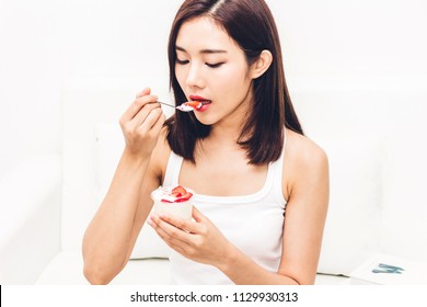 Woman eating yogurt with fresh strawberry while relaxing on sofa at home.dieting concept.healthy lifestyle