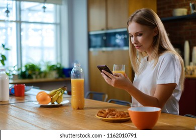 Woman eats breakfast and uses her mobile phone
