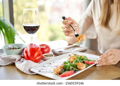 Woman eats Delicious dish with grilled shrimps, slice grapefruit and arugula salad and spicy fried prawns. Restaurant menu, natural and organic food concept.