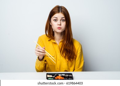 A woman eats, a woman is distracted from eating
