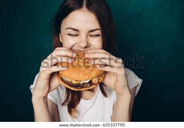 A woman eats with great pleasure, a woman eats a burger, food