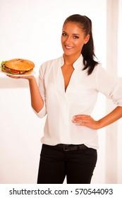Woman eats hamburger isolated over white background.