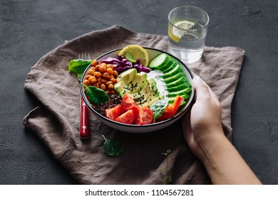 Woman eats healthy food on dark background. Buddha bowl. Clean and balanced healthy food concept