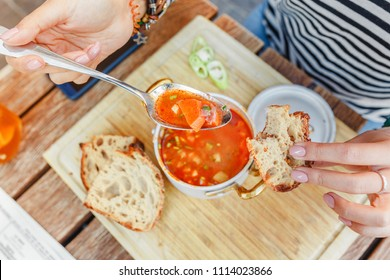 A woman eats a traditional Hungarian goulash or tomato soup from a saucepan in an outdoor restaurant