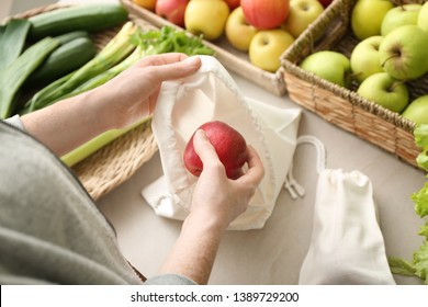 Woman with eco bag buying fruit in shop. Zero waste concept