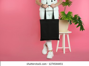 Woman with eco bag near green plant on color background. Mock up for design