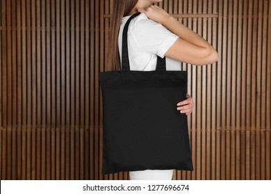 Woman with eco bag on wooden background. Mock up for design