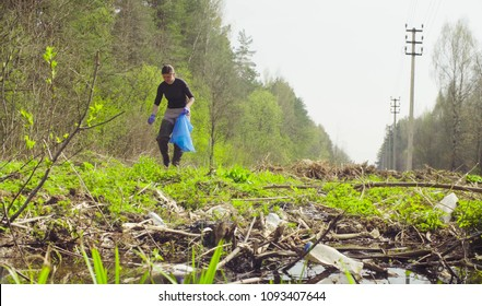The woman ecologist collecting garbage in a garbage bag in the forest.