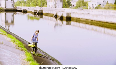 Woman ecologist going down to the river in the city. Damage appreciate to nature in an urban environment