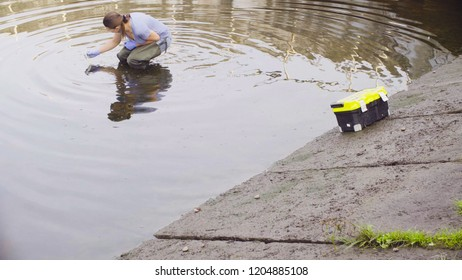 Woman ecologist measuring pH of the water in the city river. Damage appreciate to nature in an urban environment