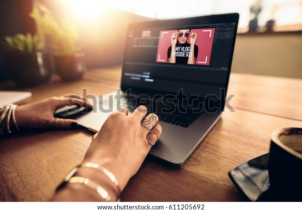 Woman editing video on laptop computer for her vlog. Woman wearing fashionable rings working on laptop on a wooden table.