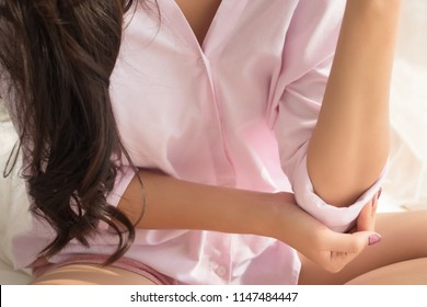 woman with elbow joint pain symptoms; portrait of asian woman suffering from arm pain injury, gout or arthritis or inflammation symptoms at elbow bone joint; asian 20s young adult woman model