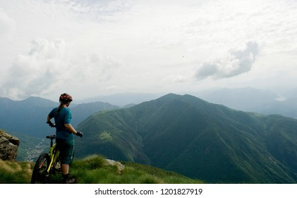 woman with electric bicycle, e-bike, ebike, mtb, look mountain and forest, summer, sport, adventure, freedom, alps, Mount Legnone, Como Lake, Italy