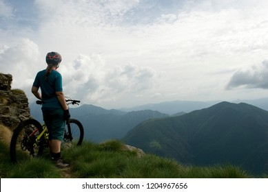 woman with an electric bicycle, e-bike, ebike, mtb, observes horizon, mountains, summer, sport, adventure, freedom, alps, Mount Legnone, Como Lake, Italy