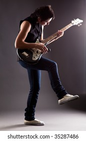 Woman with electric guitar on gray background