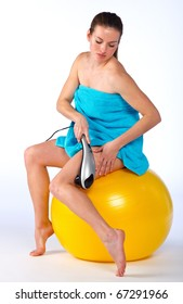 woman with electric massager sitting on pilates ball