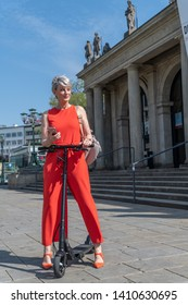 Woman with electric scooter in the city in front of theater with smartphone