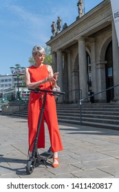 Woman with electric scooter in front of theater writes message
