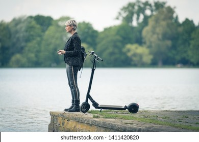 Woman with electric scooter at the lake