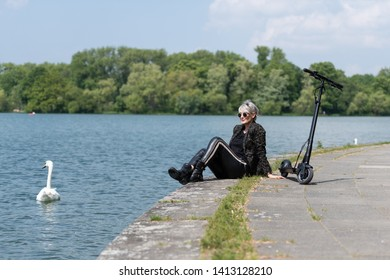 Woman with electric scooter takes a break at the lake