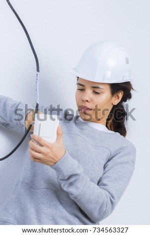 woman electrician fixing socket