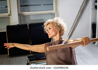 Woman in the elegant clothes practicing stretching exercise on tower reformer in gym.