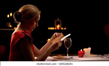 Woman in elegant dress looking at restaurant bill, having dinner alone, break up