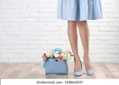 Woman and elegant handbag with spring flowers near white brick wall, closeup. Space for text