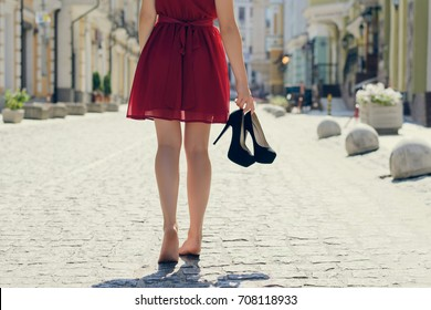 Woman in elegant red dress holding her high heel shoes in hands and walking barefoot, coming back home after party in the morning; view from back; city on the background