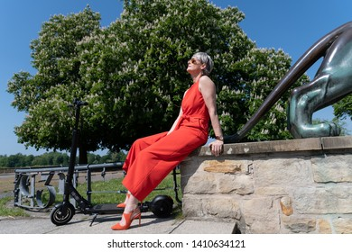 Woman with eletroroller enjoys the sun in a park