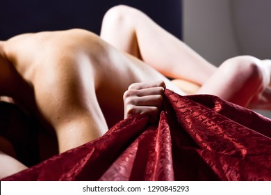 Woman embrace lover by legs. Female orgasm. Sex and pleasure concept. Passionate couple have sex make love. Feeling of intense sexual pleasure. Hand squeeze bedclothes. Naked lovers passionate sex.