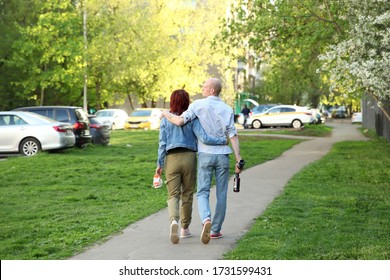 Woman in an embrace with a man who is holding beer bottles walking down the street in the spring. Moscow.11.05.2020