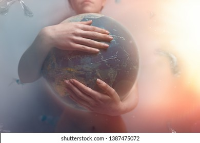 Woman embracing the globe of planet Earth. The concept of preserving the environment and love for your planet. Tint red and grey. Light.