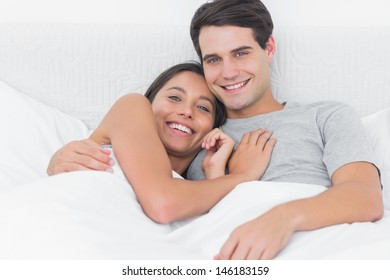 Woman embracing her partner in bed in the bedroom