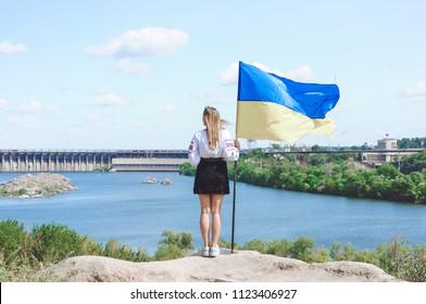 Woman in embroydery standing with Ukrainian flag on Khortytsya island