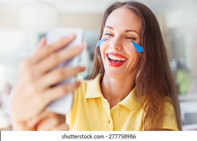 """woman with """"emoji"""" style tears of her laughing face. woman reading jokes in internet from mobile phone"""