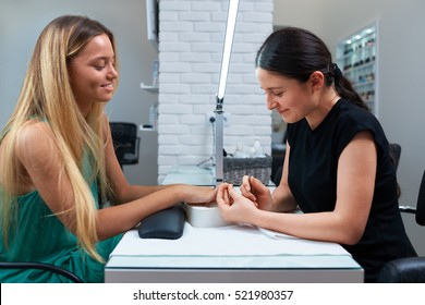 woman employee of a beauty salon, makes the procedure for nail care client smiling