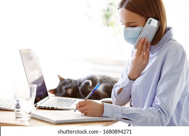 Woman employee in mask with laptop computer in self isolation working from home, coronavirus covid-19 quarantine. Remote working of business worker, online education. Prevention of virus spread