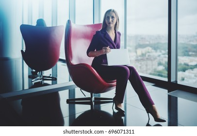 Woman employee in purple suit is sitting on armchair in luxury office, holding partly closed net-book and seriously looking into the camera, cityscape view from high point in defocused background