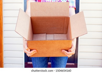 Woman with empty open cardboard box stands near her house. Close-up