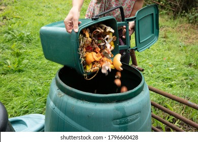 A woman emptying a home composting bin into an outdoor compost bin to reduce waste