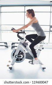 Woman energetically riding exercise bike in gym