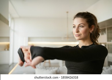 A woman is engaged in aerobics with her health doing stretching and cardio exercises. Brunette of Caucasian appearance. workout fitness gym at home in the living room, comfortable sportswear in black.