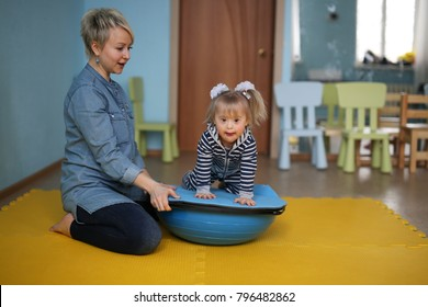 A woman is engaged with a child on a balancer beam for yoga Exercise Fitness Balance board, lifestyles and toning.