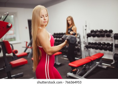 Woman engaged in a group, a body of body fitness with dumbbells. Elbow bending