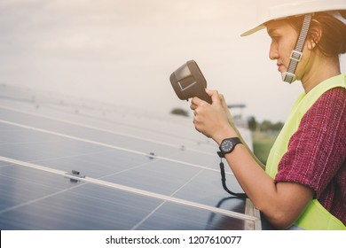 woman engineer checking heat of solar panel and using ir camera to scan heating of panel at solar power plant ; infrared camera using for checking and maintenance power plant of solar